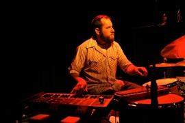 Jason Slota performing with John Vanderslice